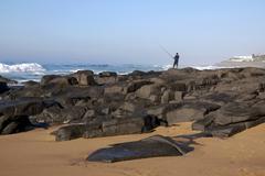 lone fisherman on rocks at ballito beach - stock photo