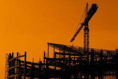 derrick cranes in construction site at sunset time - stock photo