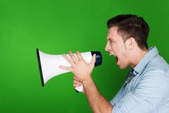 Angry young man yelling into a megaphone Stock Photos