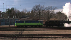 An electric locomotive is being towed by an old steam locomotive Stock Footage