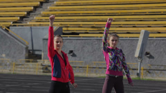 Young girls spend training exercises before the race.Warm up the shoulder girdle Stock Footage