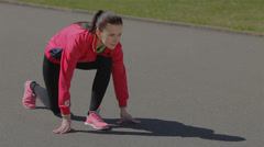 Young girl doing a race at the stadium. Become a rack to start, starts running. - stock footage