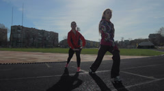 Young girls spend training exercises before the race. leg muscle warm up exercis Stock Footage
