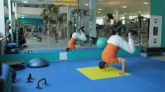 Sport SS 003 young man doing exercise handstand to strengthen back and abdominal - stock footage
