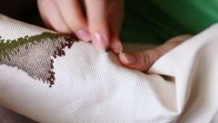 Woman hands doing cross-stitch. A close up of embroidery Stock Footage