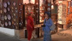 Two women in straw hats, watching  traditional ceramic plates. Greece Stock Footage
