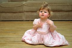 Astonished small girl in pink dress on wooden floor at home Stock Photos