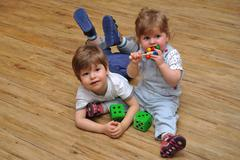 Happy curious brother and sister are sitting and lying on wooden floor with toys - stock photo