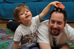 Son and father playing with cars on carpet at home - stock photo