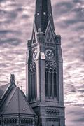 closeup of a red brick steeple with dramatic sky, vintage color filter - stock photo