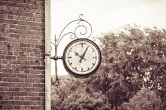 old outdoor analog clock on a wall, vintage color filter - stock photo