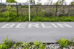 asphalted way in a park with berlin lettering on it - stock photo
