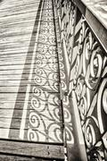 vintage style detail of an old bridge with decorated handrail - stock photo
