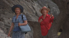 Two women, tourists in straw hats, walking near the rock of Lindian Acropolis. - stock footage