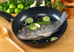 raw tilapia with condiments in frying pan - stock photo