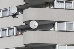 Detail of a sparse gray house with two  satellite dishes Stock Photos