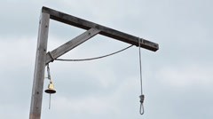 Wooden gallows with swinging noose rope and golden bell against cloud sky Stock Footage