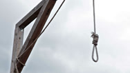 Stock Video Footage of Wooden gallows with swinging noose rope against cloud sky