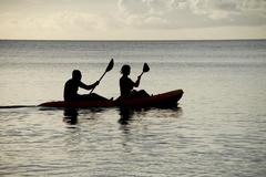 Kayakers silhouetted on the ocean - stock photo