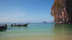 Longtail boat arriving to a paradise beach with an impressive limestone rock Stock Footage