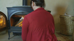 Woman tends to a cottage fire - dolly Stock Footage