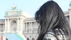 Woman studying map sitting in front of the Austrian National Library Stock Footage