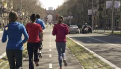 Stock Video Footage of Young joggers running by the city street HD