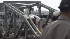 PORT, QUAY & JETTY:  ASIA - Oblique view of workers on footbridge Stock Footage
