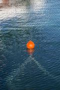 orange buoy in blue ocean water - stock photo