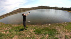 Young child casting fishing pole into lake Stock Footage