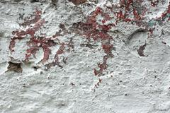 old concrete wall with multi-layer shelled surface - stock photo