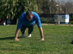 Young man doing press ups in the park NTSC Stock Footage