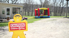 Kids bouncing and playing with caution sign Stock Footage