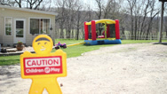 Stock Video Footage of Kids bouncing and playing with caution sign