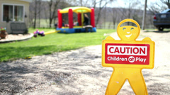 Children at play Caution sign with kids in background Stock Footage