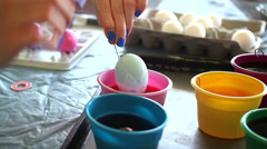 Holding egg half way down in coloring dye Stock Footage