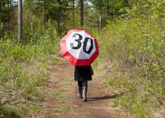 Woman in the forrest with a traffic sign umbrella Stock Photos