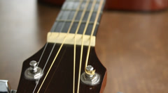 Acoustic guitar headstock and neck indoors, close-up, camera moving Stock Footage