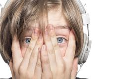 Desperate male teenager with headphones covering his face with hands Stock Photos