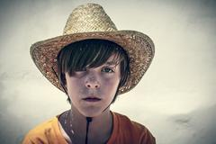 Portrait of a male teenager with straw hat, vintage color filer Stock Photos
