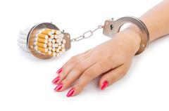 Addition concept with cigarettes and handcuffs Stock Photos