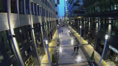 People walk by narrow street between two office buildings Stock Footage