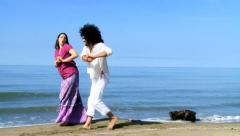 Man and woman dancing funny on the beach Stock Footage