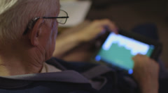 Elderly man playing solitaire on iPad Stock Footage