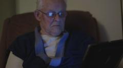 Elderly man reading on iPad tablet Stock Footage