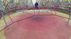 Brother and sister play on rope construction at playground Stock Footage