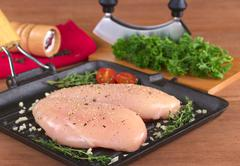 raw chicken breast in frying pan - stock photo