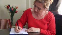 Woman thinking and writing Stock Footage