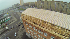 Wooden frame of roof on brick building near road with traffic Stock Footage