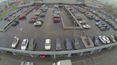 People walk by parking with many cars near shopping center Stock Footage
